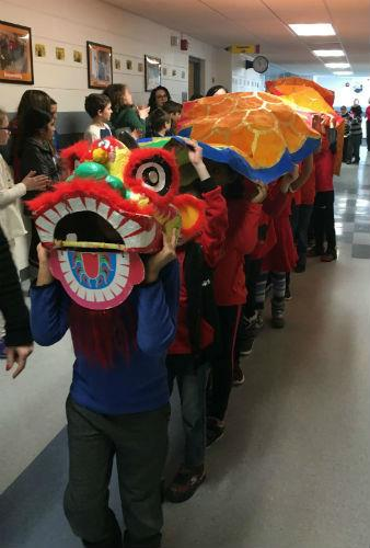 Students walk the hall in dragon costume