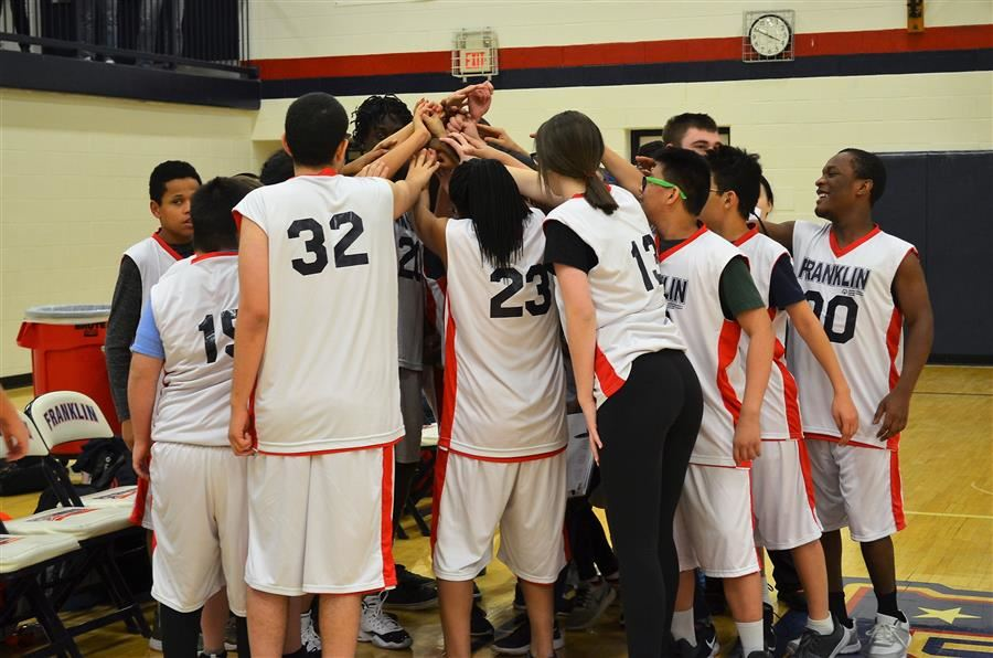basketball players in huddle