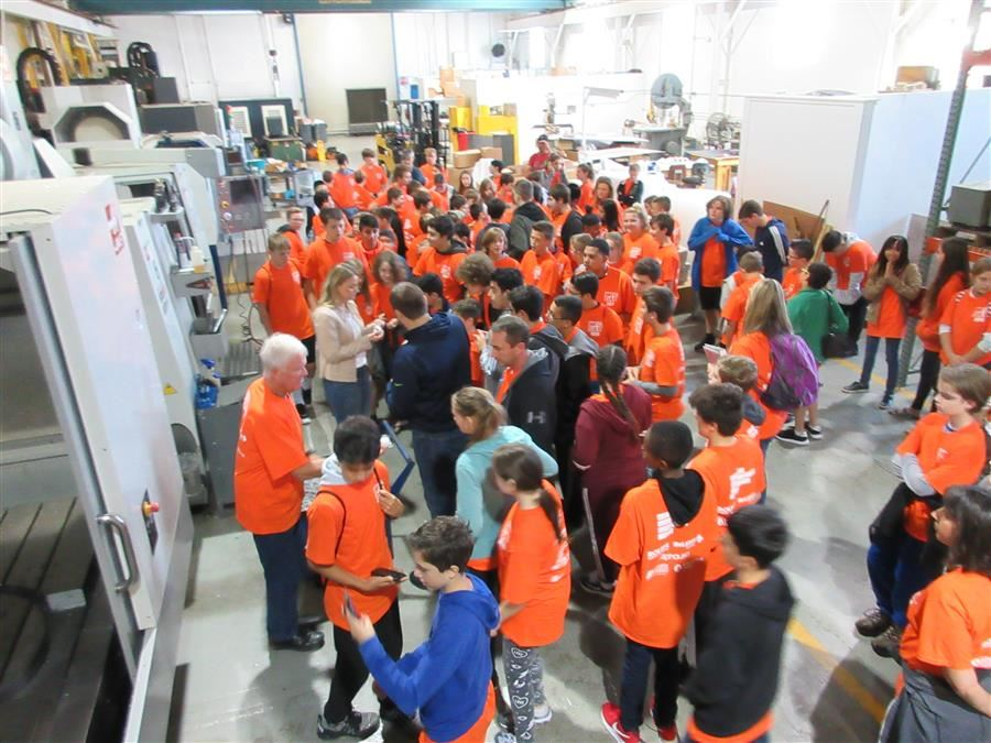 students gathered around a machine at manufacturing facility